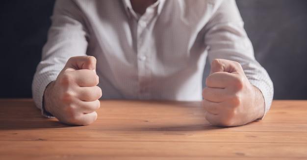 Puños masculinos sobre la mesa.