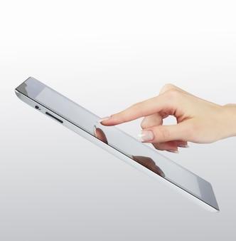 Punto de la mano de la mujer en el marco digital electrónico moderno con pantalla en blanco