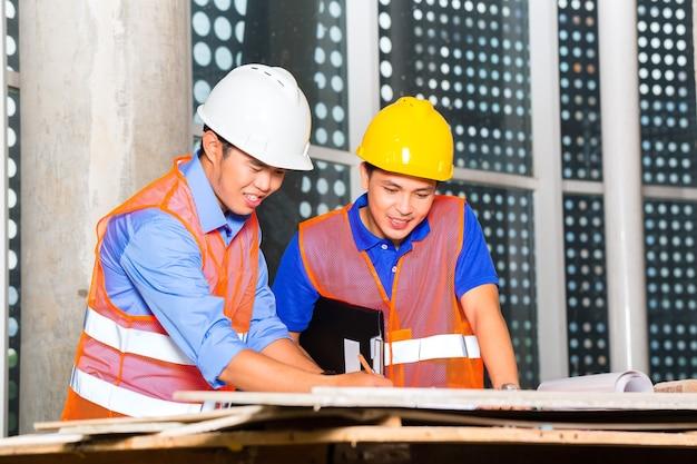 Punto de supervisor y arquitecto chino en el sitio de construcción en un plan de construcción