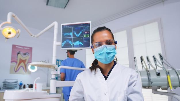 Punto de vista del paciente al estomatólogo que pone máscara de oxígeno antes de la cirugía dental sentado en una silla estomatológica. médico y enfermera que trabajan en la oficina de ortodoncia moderna con guantes y máscara de protección