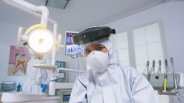 Punto de vista del paciente del dentista explicando el tratamiento de los dientes con traje protector covid en la nueva oficina estomatológica normal. estomatólogo en equipo de seguridad contra coronavirus durante el control de atención térmica del paciente.