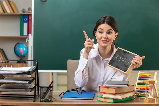 Puntos impresionados en la joven maestra sentada a la mesa con herramientas escolares sosteniendo una mini pizarra en el aula