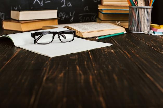Pupitre en el aula, con libros sobre fondo de pizarra con fórmulas escritas