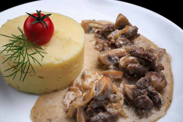 Puré de papa con champiñones y salsa en un plato blanco