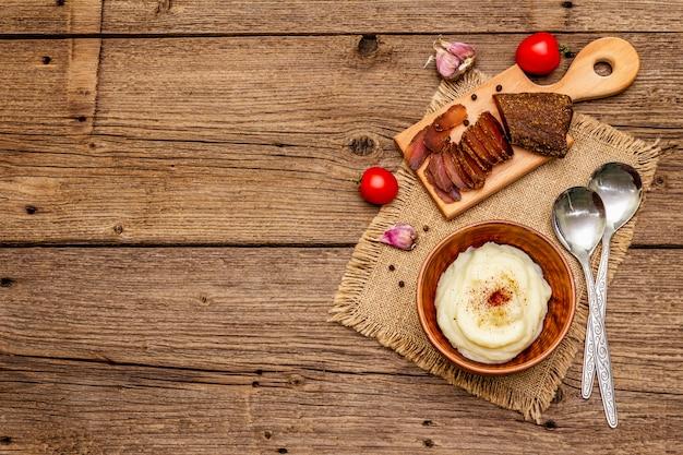 Puré de papas casero con ajo y tomates frescos y pastrami. servilleta de tela de saco