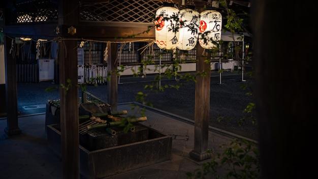 Purificación lavándose las manos en la fuente del santuario en kioto. agua que corre de la caña de bambú en japón. entrada de un templo sintoísta japonés.