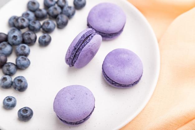 Púrpuras macarons o pasteles de macarrones con arándanos en placa de cerámica blanca sobre un fondo de hormigón gris vista superior, enfoque selectivo.