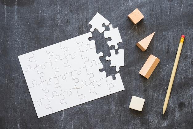 Puzzle con formas y pluma en la pizarra