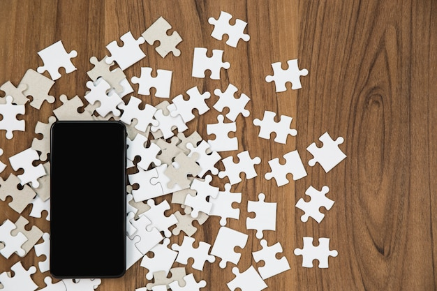 Puzzle de piezas y smartphone en mesa de madera.