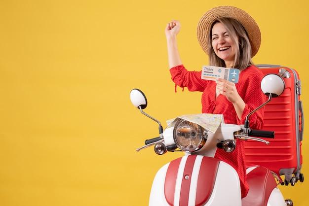 Pverjoyed señorita en vestido rojo sosteniendo boleto en ciclomotor