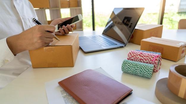 Pyme empresario de pequeñas empresas, joven asiático que trabaja con una computadora portátil y una caja de embalaje de entrega
