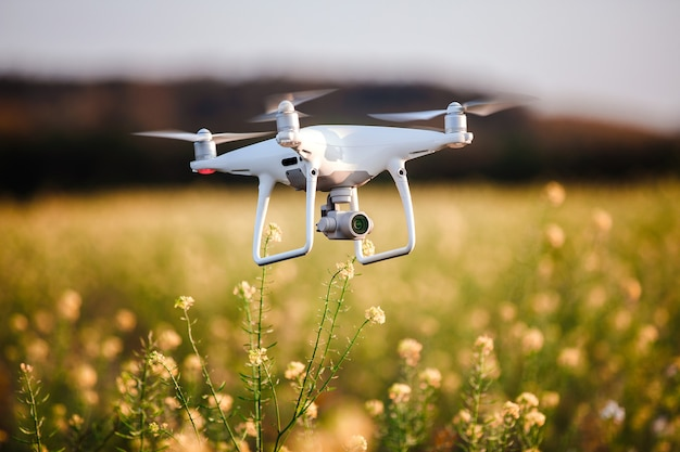 Quad helicóptero drone en campo amarillo