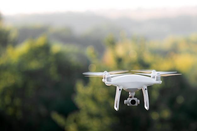Quadcopter drone volando con una cámara sobre un lago.