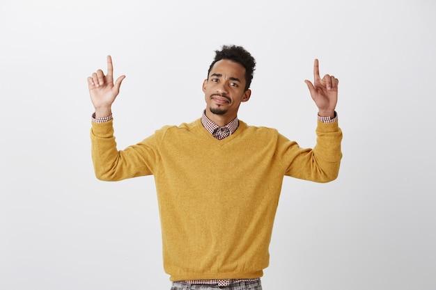 Que decepcion. retrato de chico americano dudoso disgustado con peinado afro levantando las manos y apuntando hacia arriba con los dedos índices, expresando disgusto y duda, de pie