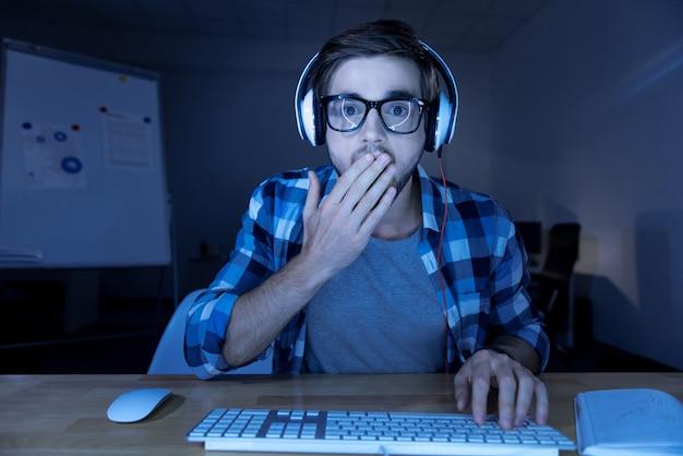 Qué es. asombrado joven agradable sentado en la computadora portátil y tapándose la boca mientras ve algo sorprendente en la pantalla