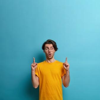 Qué espacio de copia increíble. hipster maravillado mantiene la boca abierta, señala con ambos dedos índices hacia arriba, sorprendido e interesado en mucho, usa camiseta amarilla, gesticula contra la pared azul