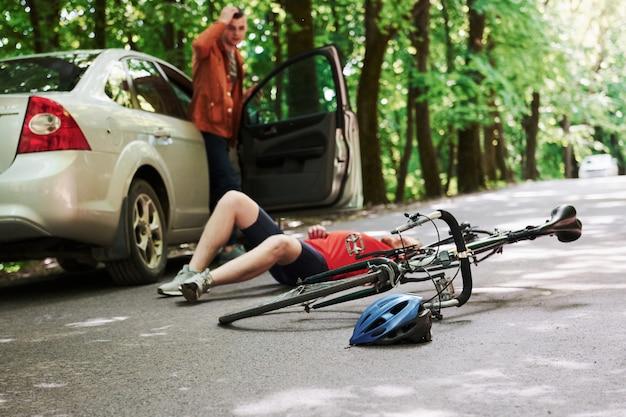Qué he hecho. víctima en el asfalto. bicicleta y accidente de coche de color plateado en la carretera en el bosque durante el día