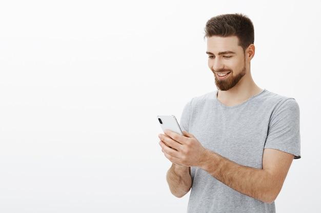 Qué placer mirar la cuenta bancaria llena de dinero. retrato de feliz elegante y guapo modelo masculino con barba sosteniendo smarpthone mirando la pantalla del teléfono móvil con alegría y sonrisa alegre