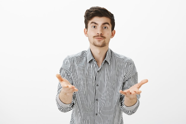 Que quieres de mi. retrato de hombre barbudo guapo cansado molesto en camisa a rayas, tirando de las manos hacia