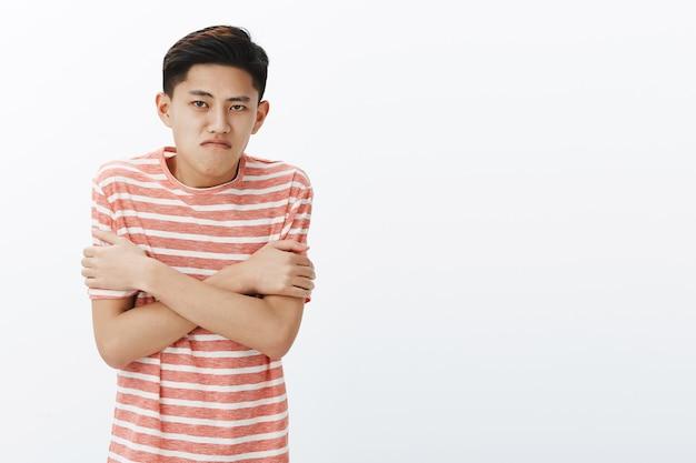 Por qué tan frío como en la nevera. chico adolescente asiático intenso disgustado en camiseta a rayas temblando abrazándose a sí mismo con las manos cruzadas contra el pecho, frunciendo los labios
