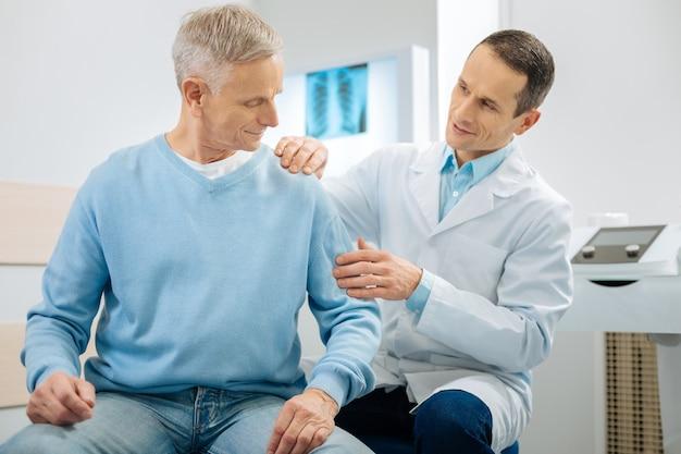 Qué tengo que hacer. agradable agradable hombre mayor sentado en la cama y mirando su brazo mientras escucha las instrucciones de los médicos