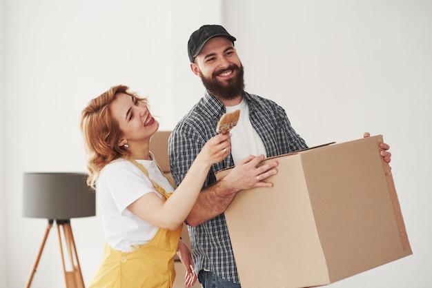 ¿qué tipo de color quieres en esa pared? pareja feliz juntos en su nueva casa. concepción de mudanza