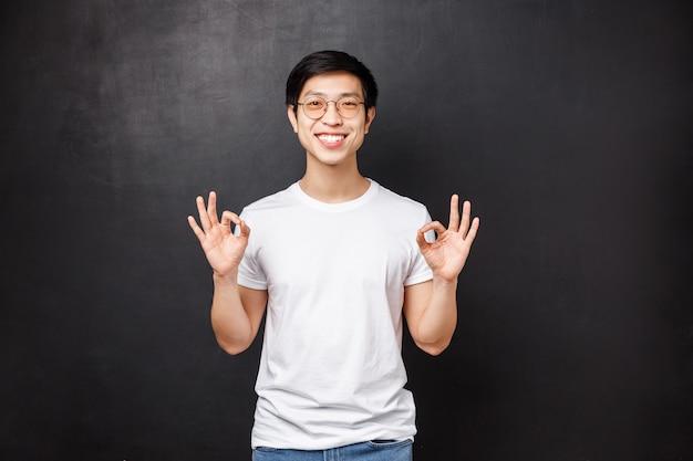Que todo esté bien, te lo garantizo. relajado, feliz, sonriente, joven, asiático, hombre, señales bien, como, asegurar, todo bien, trabajo salió bien, calificación de excelente producto, garantía de calidad