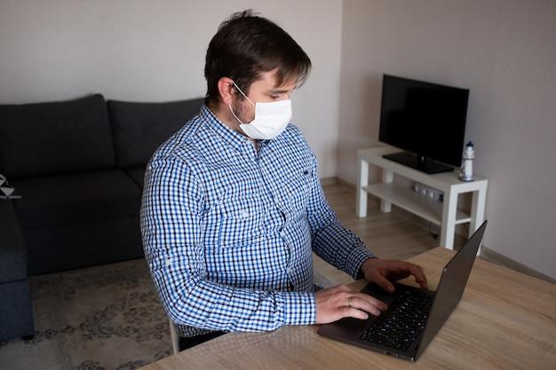 Quedarse en casa. hombre con máscara trabajando desde su computadora portátil desde casa