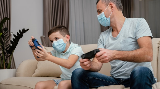 Quédate en el interior, hombre y niño jugando videojuegos.