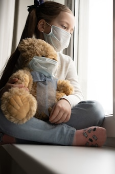 Quédese en casa, cuarentena, prevención de la pandemia de coronavirus. niño triste y su osito de peluche, ambos con máscaras médicas protectoras, se sienta en el alféizar de la ventana y mira por la ventana