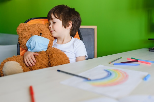 Quédese en casa debido al concepto de pandemia de coronavirus. cerrar niño pinta un arco iris en cartel de estancia en casa