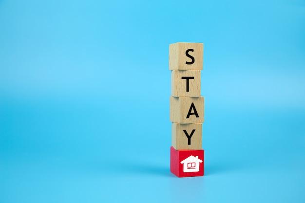 Quédese en casa mantenga los iconos seguros en un bloque de juguete de madera. conceptos para la salud y la prevención médica del coronavirus o la infección por covid-19, el distanciamiento social y el trabajo desde el hogar.