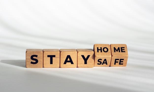 Quédese en casa, manténgase seguro mensaje en dados de madera. consejo de brote de coronavirus covid-19