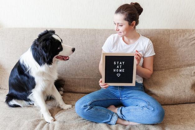 Quédese en casa manténgase seguro. mujer joven sonriente que juega con el border collie lindo del perro de perrito en el sofá en casa dentro. chica con inscripción en el tablero de letras quedate en casa cuidado de mascotas vida animal concepto de cuarentena.