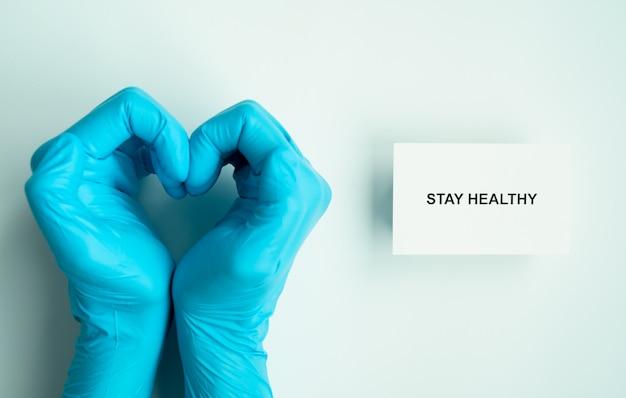 Quédese en casa y saludable para evitar la campaña de propagación de covid-19, texto en papel con las manos del médico en forma de corazón con guantes azules