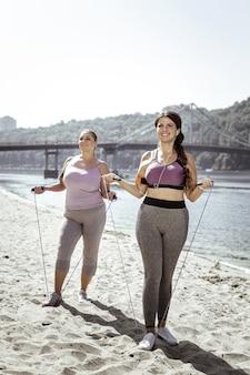 Quema las calorías. mujeres alegres positivas sosteniendo sus cuerdas de saltar mientras se preparan para comenzar el ejercicio