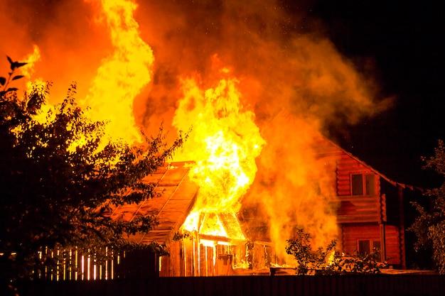 Quema de casa de madera en la noche. brillantes llamas anaranjadas y humo denso debajo del techo de tejas en el cielo oscuro, siluetas de árboles y cabaña vecina residencial. concepto de desastre y peligro.