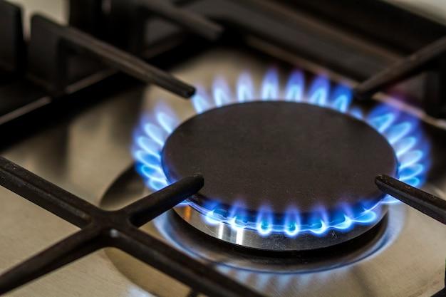 Quema de gas natural en la cocina estufa de gas en la oscuridad.
