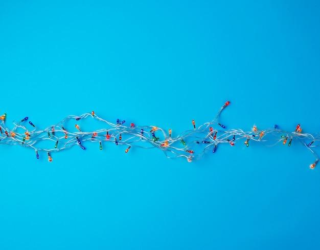Quema de guirnalda de navidad en un cable blanco con luces de colores sobre un fondo azul.