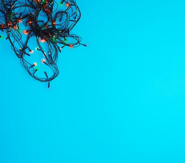 Quema guirnalda de navidad con luces de colores sobre un fondo azul.