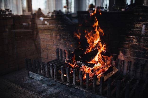 Quema de maderas con llama brillante y chispas sobre fondo oscuro