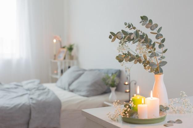 Quema de velas y eucalipto en florero en dormitorio blanco