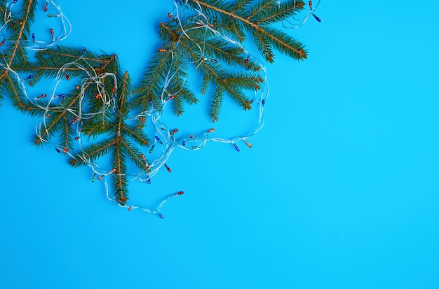 Quemando bombillas multicolores en una guirnalda con un cable blanco y ramas verdes de agujas