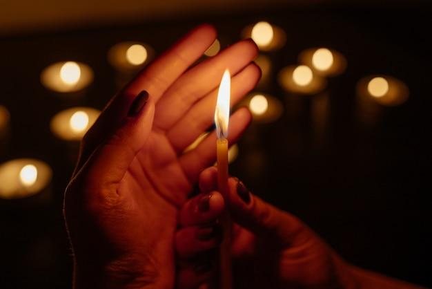 Quemando velas. vela en manos femeninas. muchas velas encendidas por la noche. muchas llamas de velas brillando.