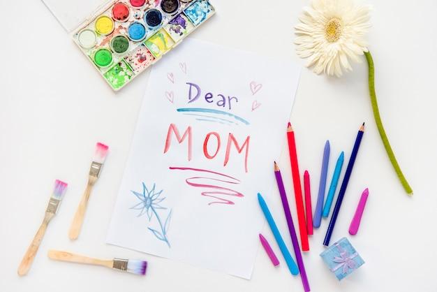 Querida mamá inscripción en papel con lápices.