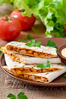Quesadilla mexicana en rodajas con verduras y salsas sobre la mesa