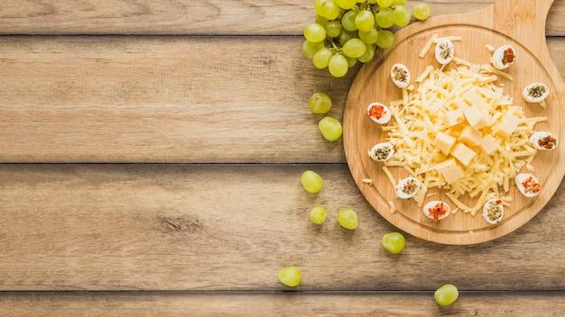 Queso con aderezos sobre tabla de cortar con uvas