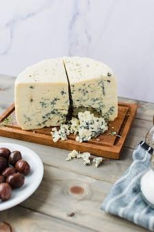 Queso azul con aceitunas en mesa de madera