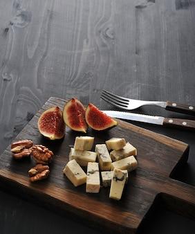 Queso azul, higos frescos y nueces sobre una tabla de madera y un cuchillo y tenedor