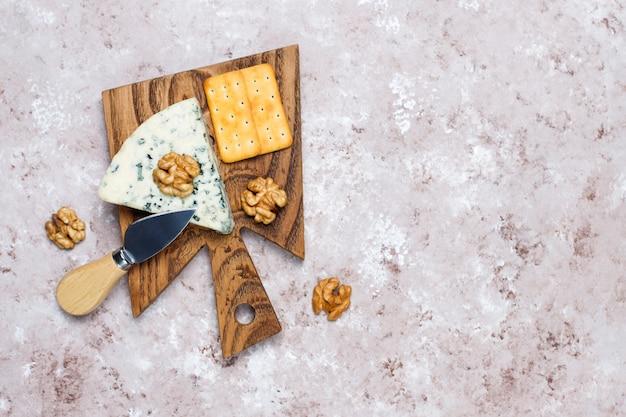 Queso azul sobre tabla de cortar de madera con miel y nueces